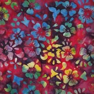 Tissu batik fleurs multicolores fond magenta